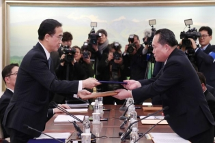 Head of the North Korean delegation, Ri Son Gwon exchanges documents with South Korean counterpart Cho Myoung-gyon after their meeting at the truce village of Panmunjom in the demilitarized zone separating the two Koreas, South Korea.