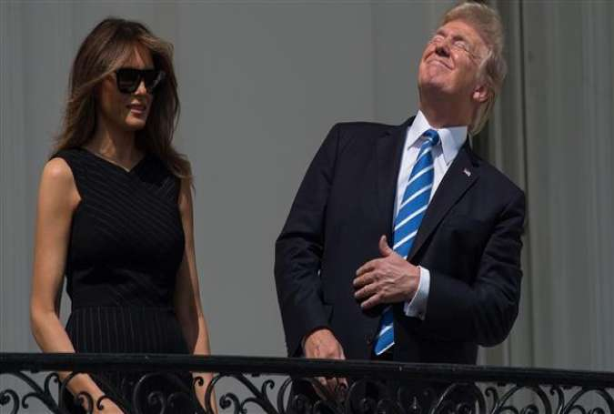 This AFP file photo taken on August 21, 2017 shows US President Donald Trump looking up a the partial solar eclipse with First Lady Melania Trump from the balcony of the White House in Washington, DC.