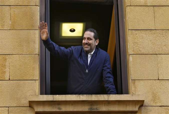 Lebanese Prime Minister Saad Hariri waves to his supporters from a window of his residence in Beirut, November 22, 2017, after returning from Saudi Arabia and putting his resignation on hold.