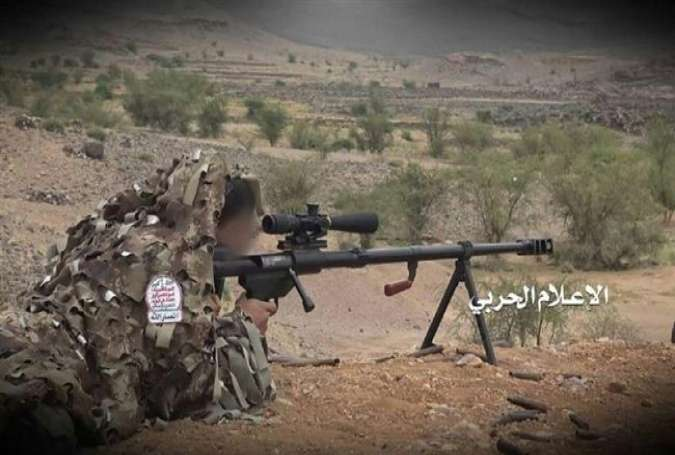 This file photo shows a Yemeni Houthi Ansarullah fighter dressed in camouflage, and aiming at a position of Saudi troops in southwestern Saudi Arabia. (Photo by the media bureau of Yemen's Joint Operations Command Center)
