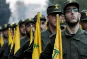 The file photo shows Hezbollah fighters holding flags of the Lebanese resistance movement during a parade in a southern suburb of Beirut, Lebanon. (AP photo)