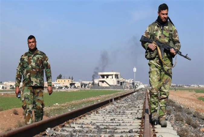 Syrian government forces walk along a railway track after taking control of the village of Abu al-Duhur on the eastern outskirts of Idlib, as they continue to battle foreign-sponsored Takfiri militants on February 3, 2018. (Photo by AFP)