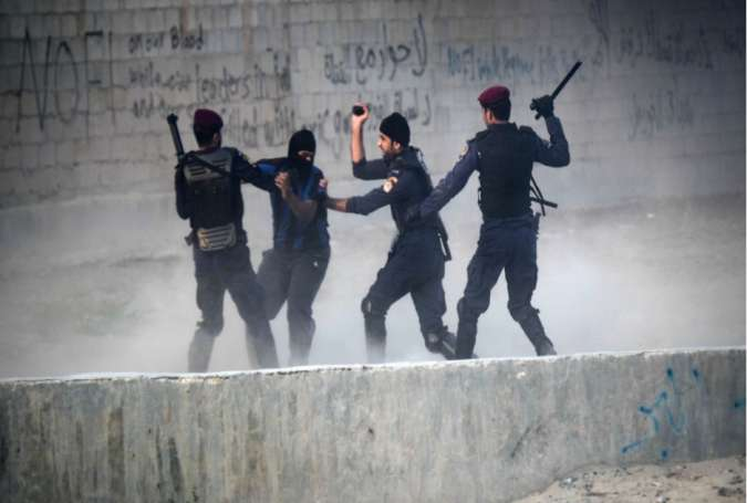 Bahraini regime forces attack a protester during demonstration against the ruling regime in the village of Shakhora, west of Manama,