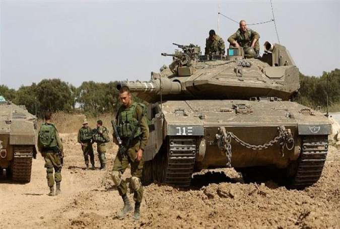 In this file picture, Israeli soldiers stand guard with their tank along the border between the Gaza Strip and the occupied Palestinian territories. (Photo by the Times of Israel)