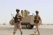 In this file picture, soldiers from the United Arab Emirates walk past a military vehicle at the airport of Yemen