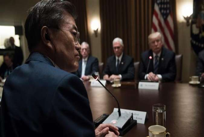 This file photo shows South Korea's President Moon Jae-in (foreground) and US President Donald Trump (background-1st-R) during a meeting at the White House in Washington, DC, on June 30, 2017. (By AFP)