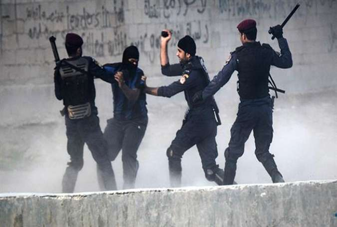 Bahraini police forces arrest a protester during a demonstration in west of the capital Mana.