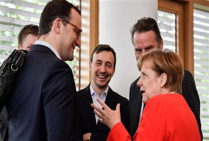 In this file photo taken on June 26, 2017 German Chancellor and leader of the CDU (Christian Democratic Union) Angela Merkel (R) speaks to CDU MP Jens Spahn (L) during a meeting of the party leadership at the CDU headquarters in Berlin. (AFP photo)