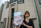 A journalist poses with a portrait of Turkish writer Ahmet Altan on June 19, 2017, in front of the Istanbul courthouse. (AFP)