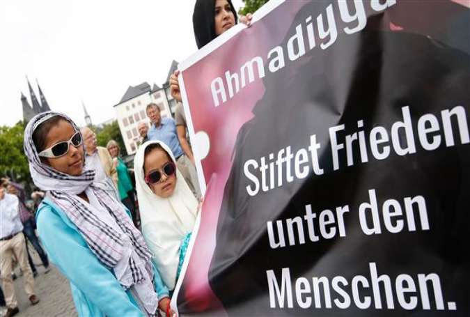 "Two girls stand next to a banner citing the Holy Quran and reading ""Make peace among the people,"" as they take part in a protest rally against terrorism and violence in Cologne, western Germany, on June 17, 2017. (Photo by AFP)"