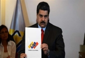 Venezuelan President Nicolas Maduro shows the document after signing the electoral guarantee agreement between the government and opposition presidential candidates, at the National Electoral Council (CNE) headquarters in Caracas on March 2, 2018. (Photo by AFP)