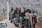 The photo shows a convoy of pro-Syrian government fighters arriving in Syria