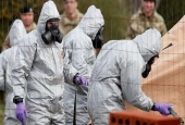British military personnel wearing protective coveralls work to remove a vehicle connected to the March 4 nerve agent attack in Salisbury, from a residential street in Gillingham, southeast England, on March 14, 2018. (Photo by AFP)