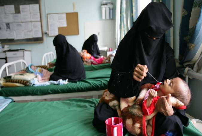 A mother spoon-feeds her sick child at health center in Yemen