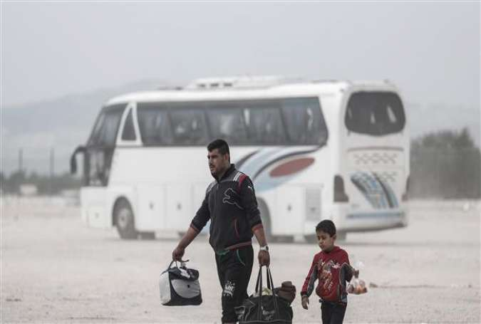 Militants and their families, who have been evacuated from a town east of the capital Damascus, carry their belongings after disembarking from a bus, which has brought them to the city of Azaz in the northern countryside of Aleppo, April 20, 2018. (Photo by AFP)