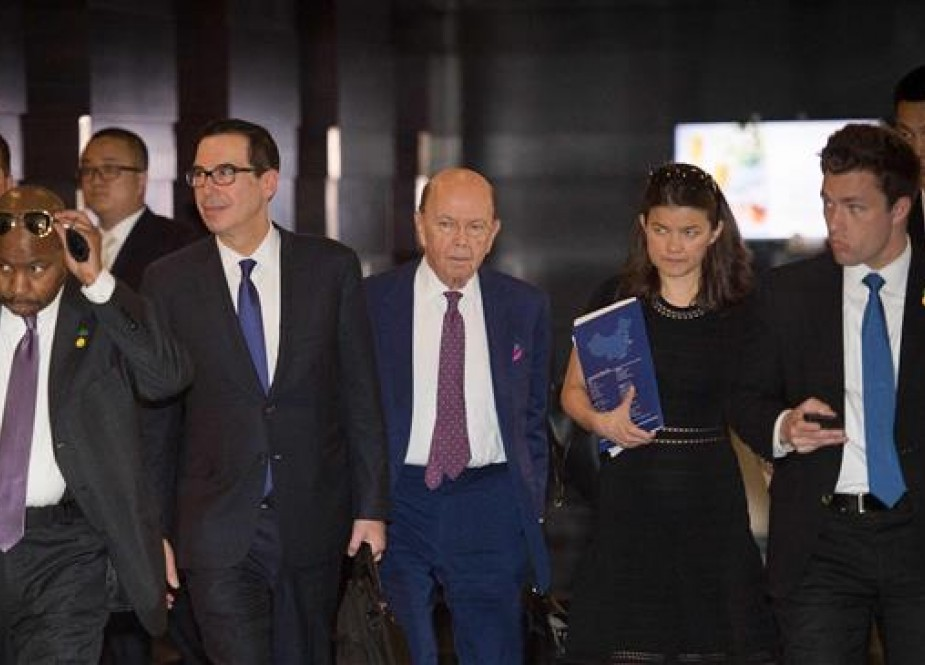This file photo shows US Treasury Secretary Steven Mnuchin (center-L) and US Commerce Secretary Wilbur Ross (center-R) walking through a hotel lobby as they head to Diaoyutai state guest house to meet Chinese officials in Beijing, China, on May 4, 2018. (By AFP)