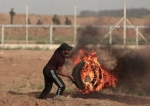 Palestinian throwing a burning tire at the Gaza Strip's border with occupied territories