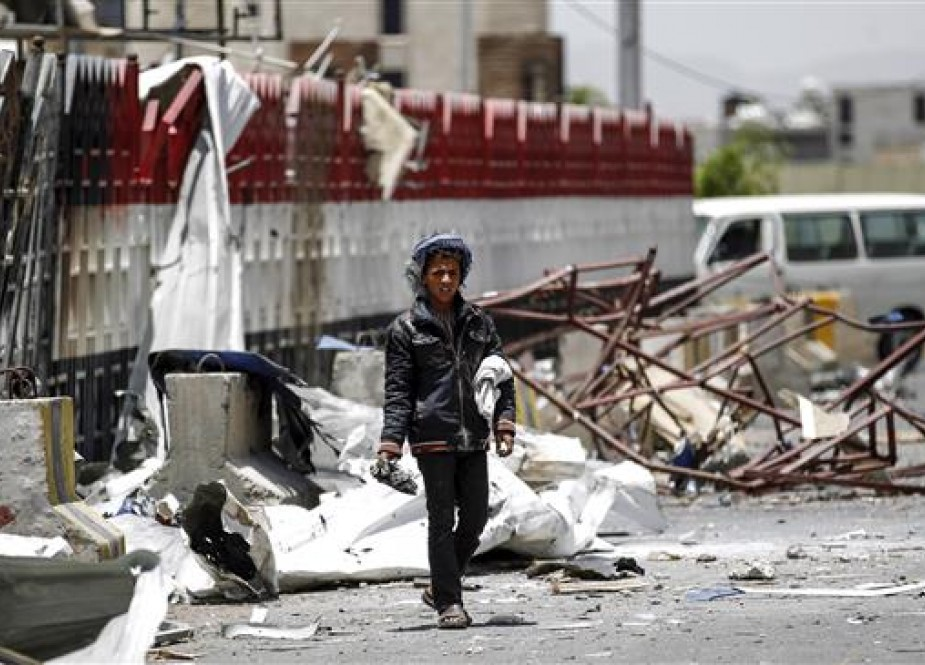 A Yemeni boy walks through the rubble and debris of a destroyed petrol station that was hit by a Saudi airstrike in the capital Sana