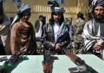 Former Taliban militants look on as they stand alongside their weapons in Jalalabad, the capital of Nangarhar province on March 19, 2014. (Photo by AFP)
