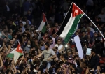 Jordanian demonstrators wave the national flags during a protest near the prime minister