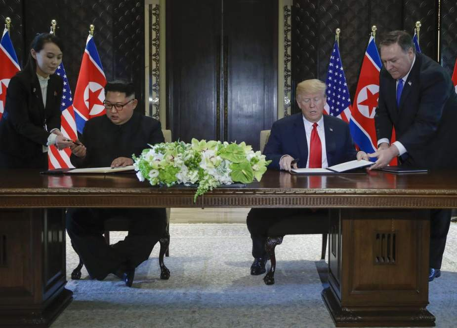 President Donald Trump and North Korean leader Kim Jong Un prepare to sign a document at a ceremony marking the end of their historic nuclear summit.