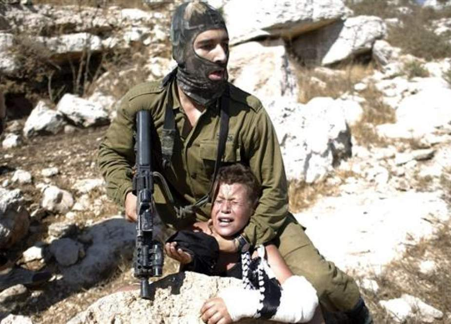 Israeli soldier detaining a 12-year-old Palestinian boy in the West Bank