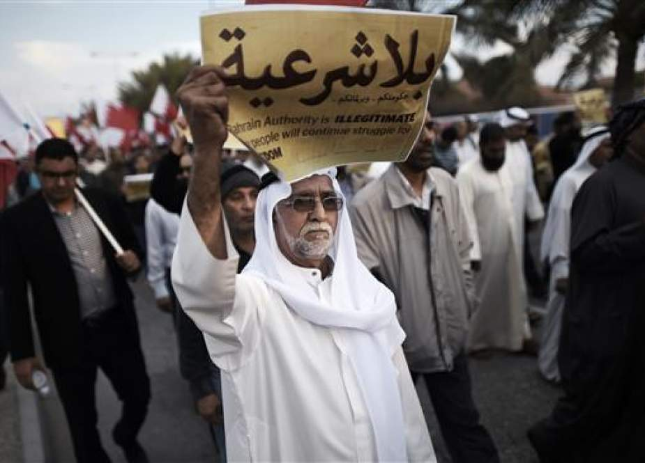 "The file photo shows a Bahraini man holding up a placard reading, ""Your government and your parliament are without legitimacy"" during an anti-regime protest in the village of Jannusan, west of the Manama. (Photo by AFP)"