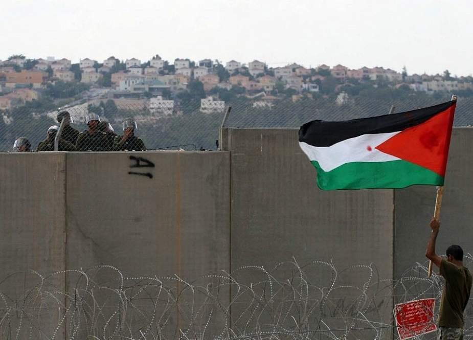 A Palestinian protester holds a flag as he stands near the security fence during a protest