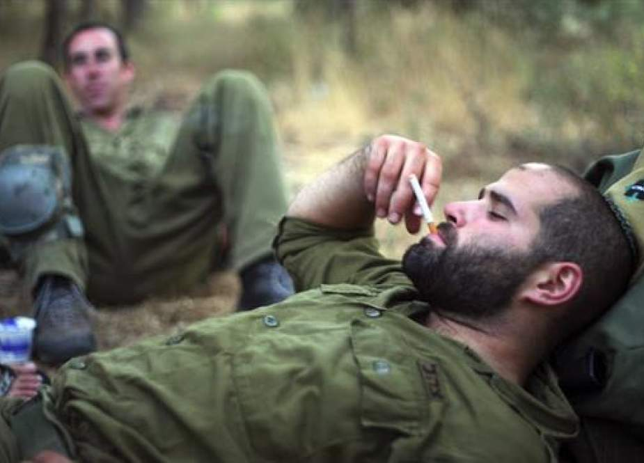 In this file picture, Israeli soldiers smoke during training in the northern part of the occupied territories. (Photo by The Times of Israel)