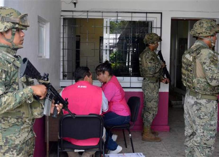 Members of the Mexican Navy stand guard next to electoral personnel and materiel, in the district 04 in Acapulco, Mexico, June 30, 2018. (Photo by AFP)
