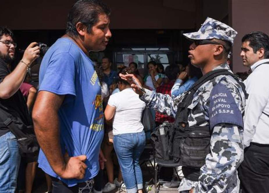 A member of the Mexican Navy speaks to a man outside a special polling station