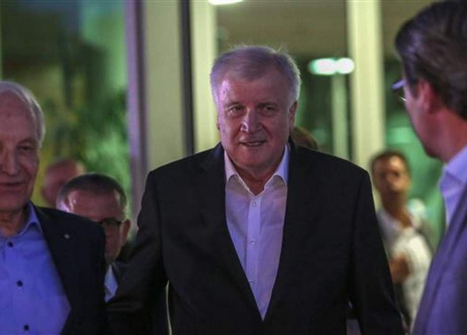 German Interior Minister Horst Seehofer (C) talks with former Bavarian State Premier Edmund Stoiber (L) and German Transport Minister Andreas Scheuer (R) as he leaves the German Christian Democrats (CDU) headquarters after a meeting with Chancellor Angela Merkel, in Berlin, Germany, on July 2, 2018. (Photo by AFP)