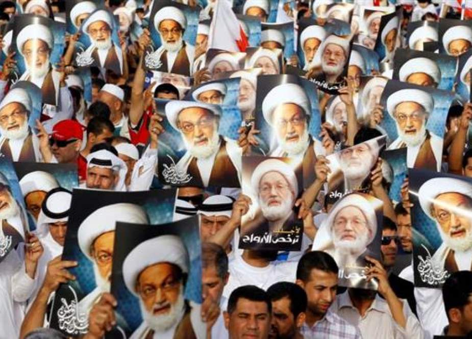 Anti-government protesters hold posters of Shia cleric Sheikh Isa Qassim in Budaiya, Bahrain, in 2013. (Photo by Reuters)