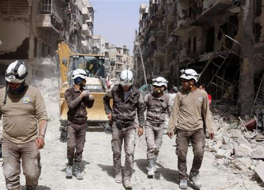 The file photo shows members of the White Helmets volunteer organization walking amid rubble in Syria.