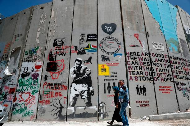Palestinian family walk past a graffiti painted on the Israeli apartheid wall in the West Bank city of Bethlehem