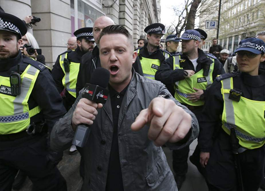 In this file photo taken on April 01, 2017 Stephen Christopher Yaxley-Lennon, AKA Tommy Robinson, former leader of the right-wing EDL (English Defence League) is escorted away by police from a Britain First march and an EDL march in central London on April 4, 2017. (AFP photo)
