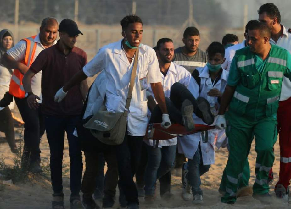 Palestinian rescuers carry a wounded protester during a demonstration near the Gaza fence, in Khan Yunis in the southern Gaza Strip on August 3, 2018.
