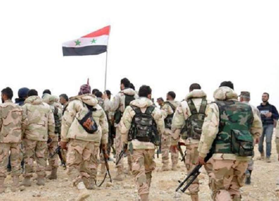 Syrian soldiers gather around a national flag in Palmyra.jpg