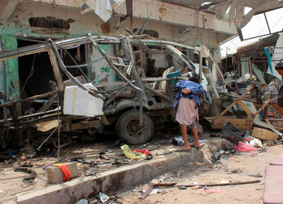 Yemenis gather next to the destroyed bus at the site of a Saudi-led coalition air strike, that targeted the Dahyan market the previous day in the province of Sa