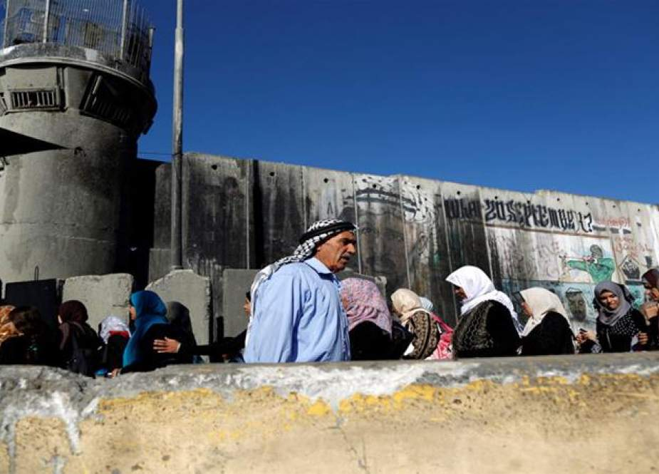 In this file picture, Palestinian women are waiting to cross through the Qalandiya checkpoint. (Photo by Reuters)