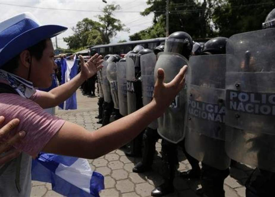 People shout at riot policemen during a protest against Nicaraguan President Daniel Ortega's government in Managua, on September 23, 2018. (Photo by AFP)