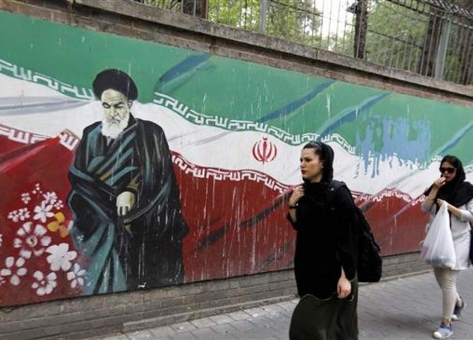 Iranian women walks past a mural on the wall of the former US embassy in the Iranian capital, Tehran, on May 8, 2018. (Photo by AFP)