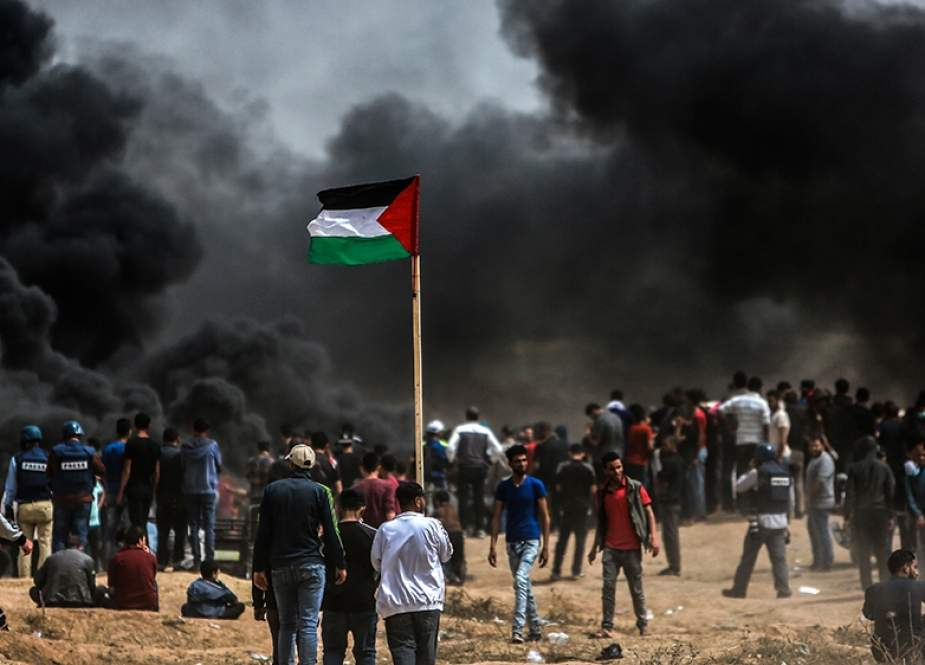 Palestinians raise their flag in front of burning tyres they lit near the border with Israel, east of Gaza City.