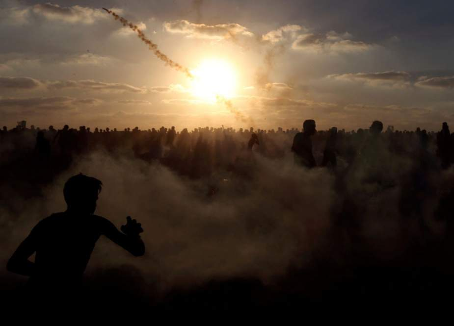 Palestinians run from tear gas during a protest calling for lifting the Israeli blockade on Gaza.jpg
