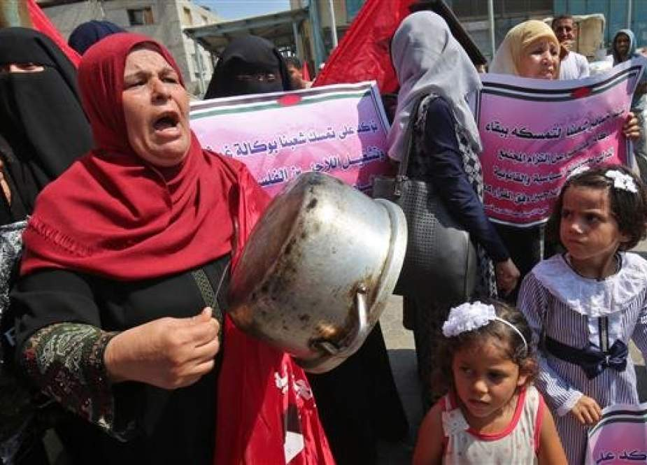 A Palestinian woman drums of a cooking pot during a protest against a US decision to cut funding to the United Nations Relief and Works Agency (UNRWA), outside an aid distribution center, in the city of Khan Yunis in the southern Gaza Strip ,on September 4, 2018. (Photo by AFP)