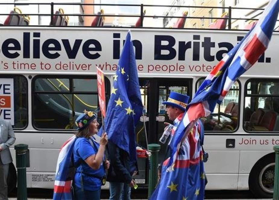 Anti-Brexit protestors carry EU flags as they stand alongside the pro-Brexit Leave Means Leave battle bus parked on the street prior to an event on the sidelines of the Conservative Party Conference 2018, in Birmingham on October 1, 2018. (Photo by AFP)