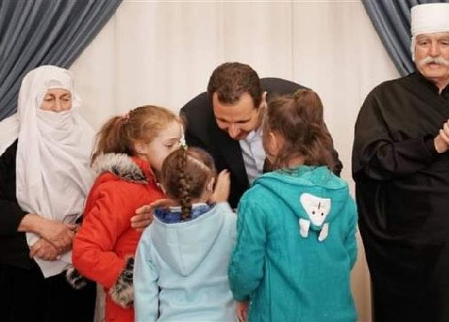 Syrian President Bashar al-Assad greets children, who were released from Daesh