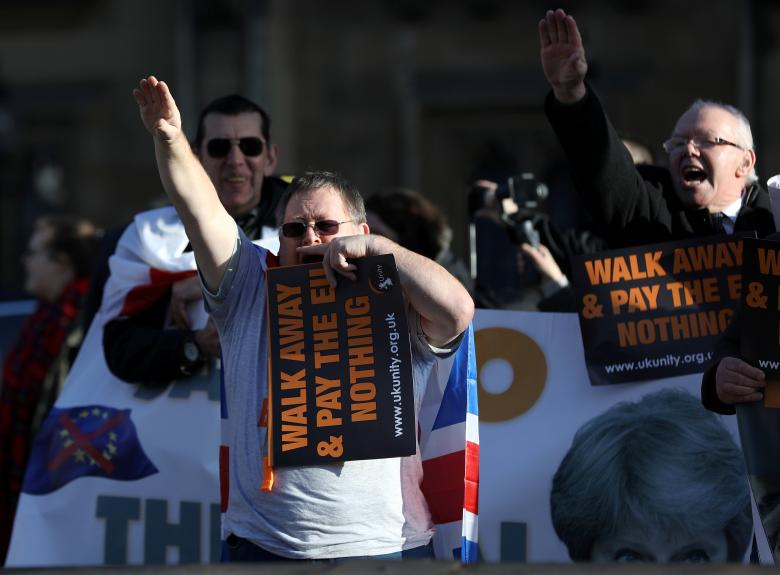 Men holding placards advocating a no-deal Brexit perform right handed salutes as they demonstrate opposite the Houses of Parliament in London, Britain, December 11, 2018.