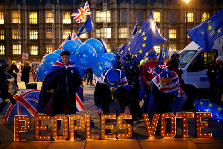Anti-Brexit protesters stand next to an illuminated sign outside the Houses of Parliament in London, December 10, 2018.