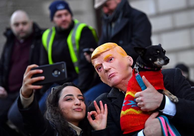 A woman takes a selfie with a demonstrator wearing a Trump mask during a pro-Brexit demonstration in central London, December 9, 2018.